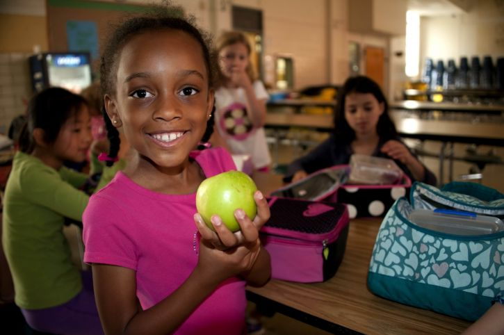 smiling-young-african-american-girl-was-holding-up-a-granny-smith-apple-in-her-right-hand-725x482